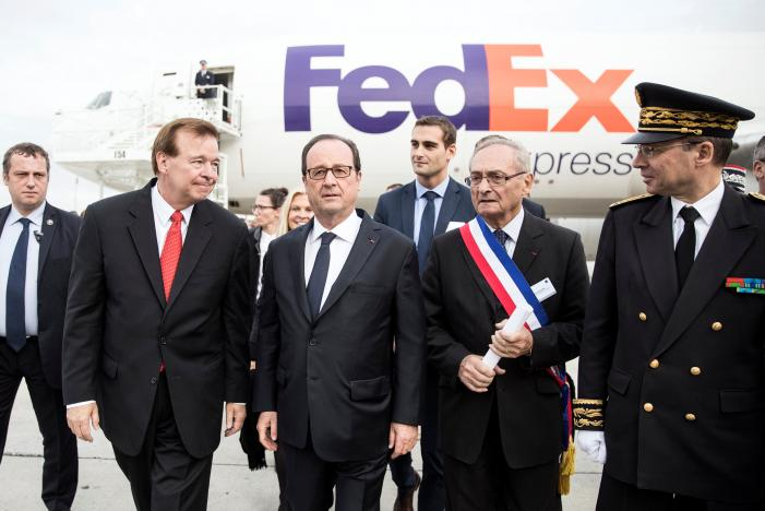French President Hollande speaks with CEO and President of Fedex Express Bronczek next to a FedEx cargo plane following the presentation of the future extension of the FedEx hub in Roissy-en-France